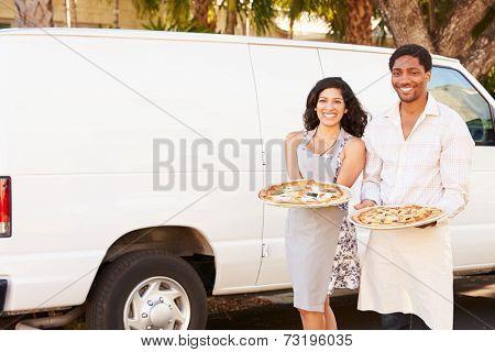 Couple Delivering Pizza Standing In Front Of Van