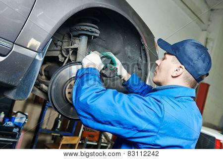 car mechanic worker repairing brakes of lifted automobile at auto repair garage shop station