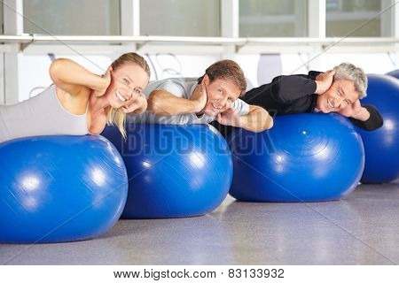 Happy group of senior people on gym balls doing back training in fitness center