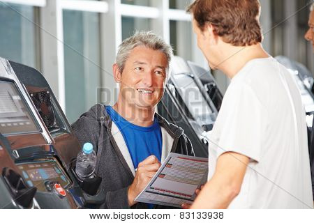 Trainer in fitness center advising senior man on a treadmill