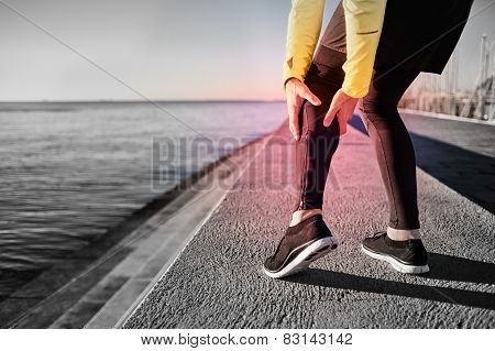 Muscle injury - Athlete running clutching calf muscle after spraining it while out jogging on the beach near ocean. Sports injury concept with running man outside. poster