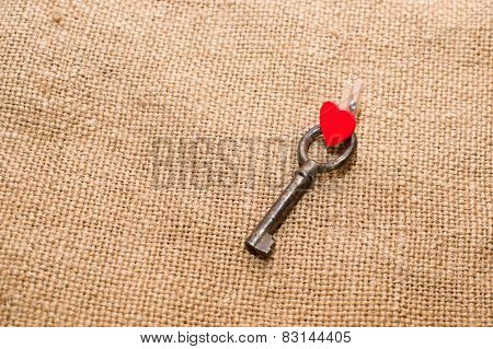One Vintage Key And A Red Heart On Old Cloth