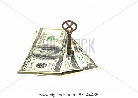 Old Key And A Few Us Dollars Banknotes On A White Background