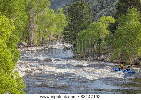 FORT COLLINS, COLORADO, USA - JUNE 4, 2011: Kayakers floating over Mad Dog Rapid on the Cache la Poudre River west of Fort Collins, Colorado as the snow pack in the high country begins to melt.