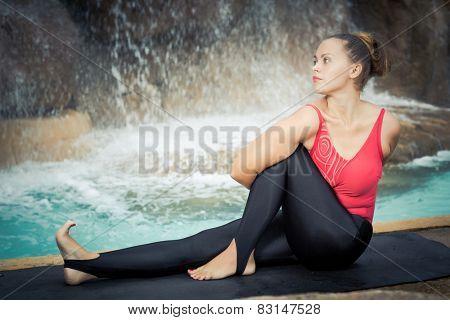 Woman practicing yoga near waterfall. Sage Twist. Marichyasana
