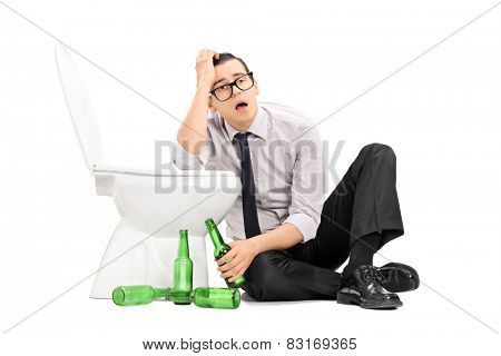 Drunk guy leaning on a toilet seat isolated on white background