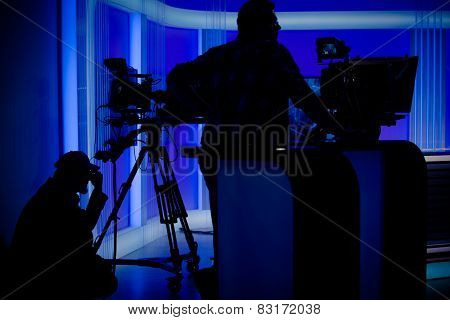 Cameraman silhouettes on a live studio news stage.Professional cameraman with headphones with camcorder in television news broadcast.Camera operators working with big broadcasting camera poster