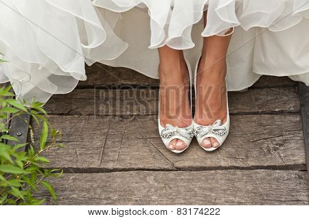 bride white open toe shoes decorated with bow and strass on wood boards