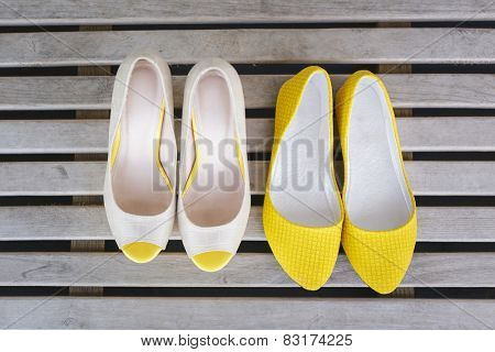 yellow ballet shoes and high heels open toe shoes on wood boards