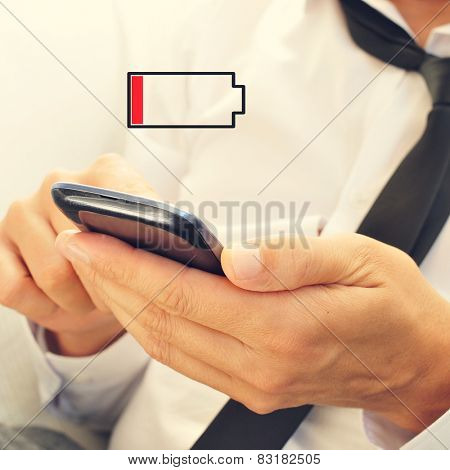 a young man using a smartphone and an illustration of a low battery