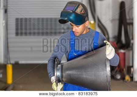 Welder Inspecting   Metal Piece For Quality Control