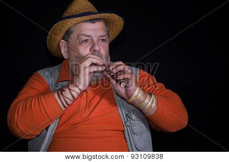 Senior musician with sopilka (Ukrainian woodwind instruments) playing on a stage poster