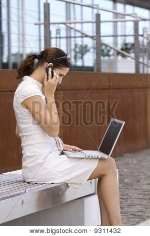 Young business female outside with laptop and cellphone