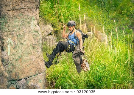man rapelling down mountainside