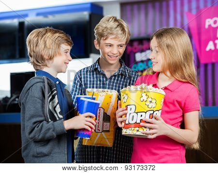Happy brothers and sister conversing while holding snacks against cinema concession stand