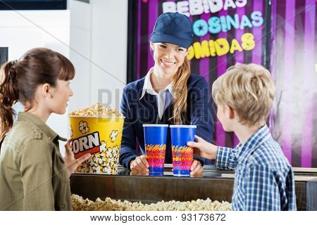 Brother and sister buying popcorn from female seller at concession stand in cinema