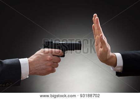 Businessman Aiming With Gun To Another Businessperson