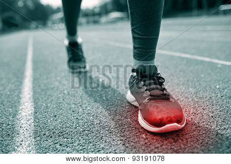 fitness, sport, sports injury, pain and people concept - monochrome close up of woman feet or legs running on track with red spot