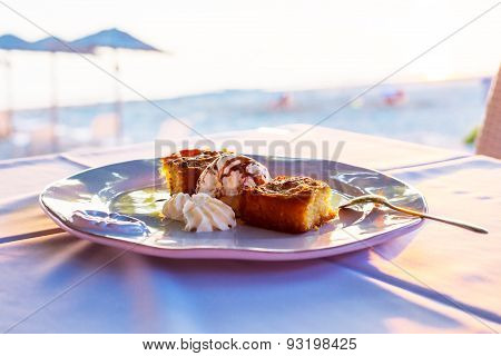 Two Pieces Of Pie With Ice Cream In A White Plate At The Evening Sun Rays And Beach Umbrellas