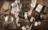Messy vintage accountant's desktop with adding machine and paper rolls he is working with the calculator poster