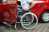 Close-up Of A Disabled Man In Wheelchair Getting In His Car poster