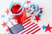 american independence day, celebration, patriotism and holidays concept - close up of juice glass, flag and candies at 4th july party poster