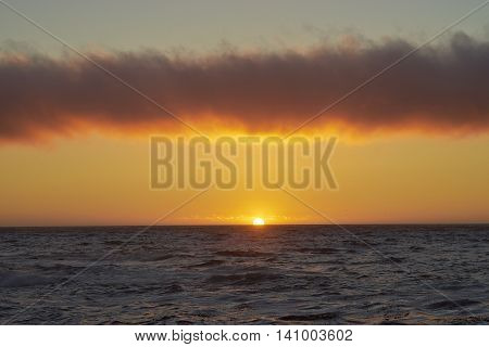 ocean at sunset with strip cloud above 17 mile drive California