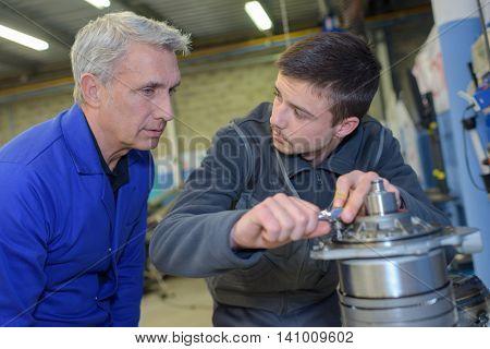 mechanic teaching an intern the best practice
