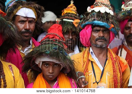 Pune, India - September 17, 2015: A groups of pilgims traditionally called as Vasudevs wearing their typical peacock feather hat.