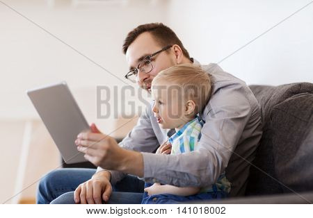 family, childhood, fatherhood, technology and people concept - happy father and son with tablet pc computer playing or having video chat at home poster