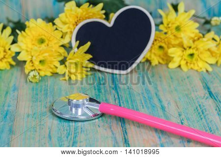 stethoscope on wooden background and heart  shape