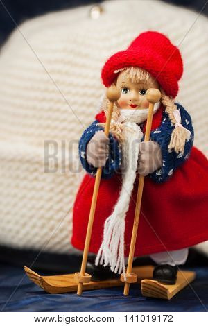 Souvenir little cross country skier on a background of white knitted hat with ear-flaps close-up, vertical