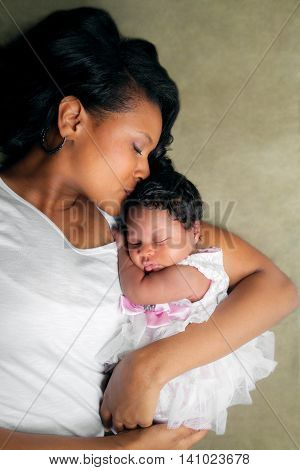 An African American mother lays on her side holding her newborn daughter. She kisses her on the top of her head.
