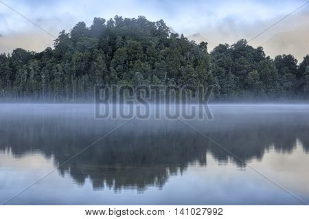 Trees reflected in Lake Kaniere South Island New Zealand