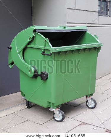 emptied garbage bin. Green waste container on a street.