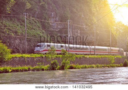 Modern high-speed train moves by the river from Interlaken Ost at early morning time. Switzerland.