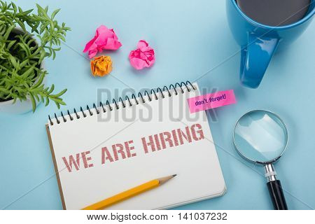 We are Hiring. Office desk table with notepad, pencil and coffee cup. Top view