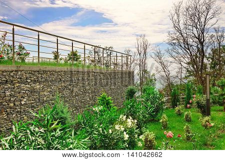 Two Level Garden Terrace On The Hill Top With Stainless Steel Guardrails And Tropical Ornamental Garden With Rocky Wall From Gabions