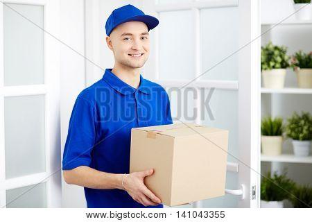 Portrait of smiling young deliveryman holding parcel