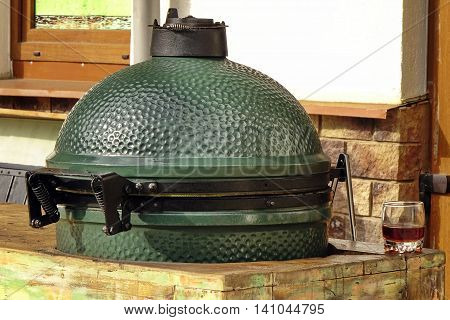 Closeup Of Green Ceramic BBQ Grill Mounted In The Table Referred To As A Kamado Or Mushikamado Japanes Cooker