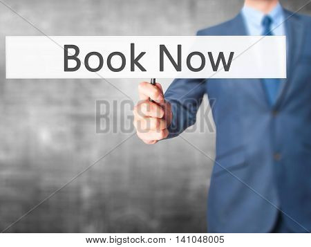 Book Now - Businessman Hand Holding Sign