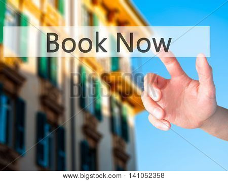 Book Now - Hand Pressing A Button On Blurred Background Concept On Visual Screen.