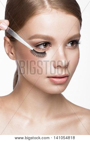 Beautiful young girl with a light natural make-up, Eyebrow Tweezers and False eyelashes . Beauty face. Picture taken in the studio on a white background.