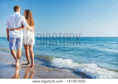 Vacation couple walking on beach together in love holding around each other. Happy interracial young couple, Asian woman and Caucasian man