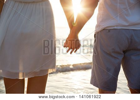 Summer couple holding hands at sunset on beach. Romantic young couple enjoying sun, sunshine, romance and love by the sea. Couple on summer vacation travel holiday poster