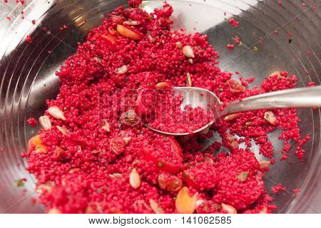 bowl of red coloured cous cous with vegetables