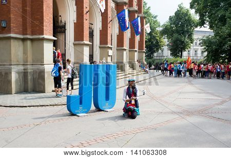 KRAKOW POLAND - JULY 27 2016: World Youth Day 2016: A girl making a selfie and other young pilgrims in front of the Collegium Novum of Jagiellonian University in Cracow