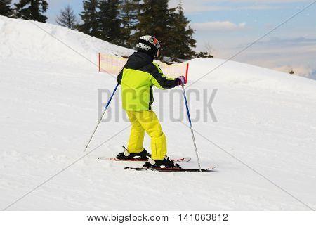 Skiing girl in ski mask and helmet on Dachstein resort in Austria Alps