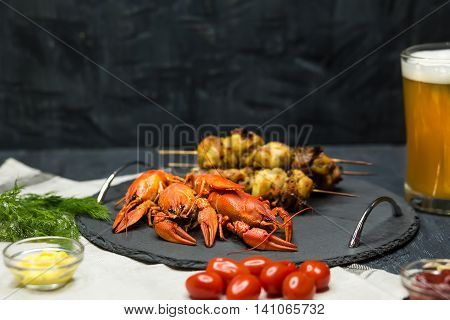Tasty boiled crayfishes barbecueand and beer on wooden table with vegetables and sauce. Concept snacks