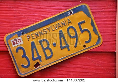 BANGKOK THAILAND-20 JUNE 2016: Yellow license plate of Pennsylvania America on red wood background at Chocolate Ville Park.
